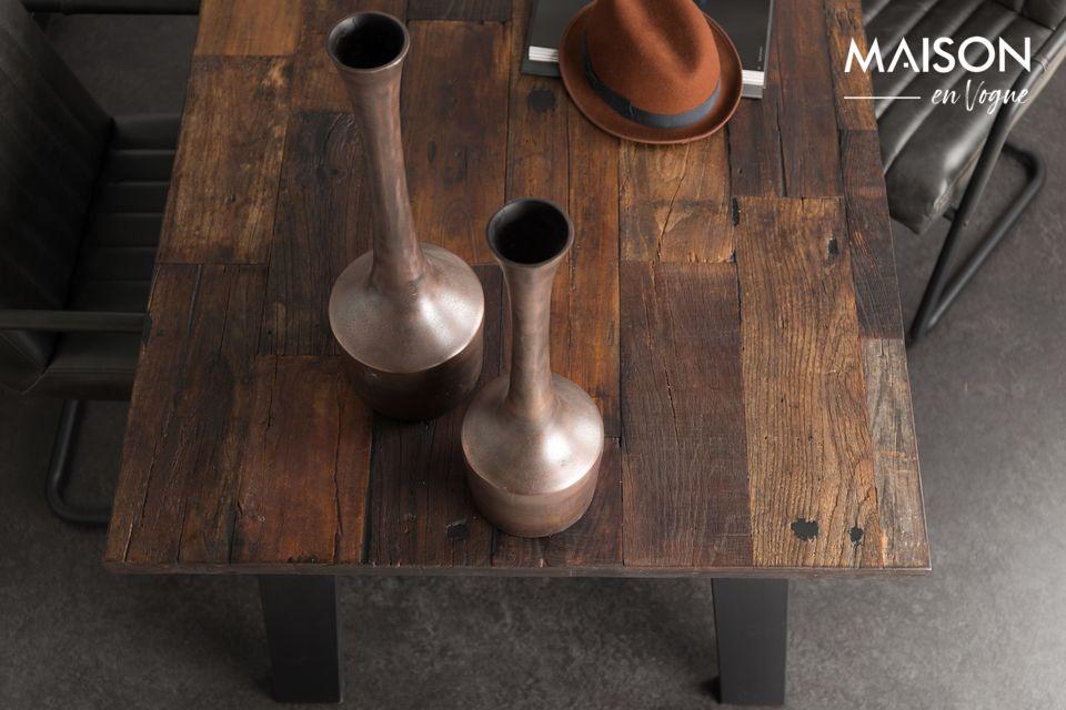 Il piano del tavolo, infatti, è realizzato in legno di olmo riciclato, recuperato da vecchie case